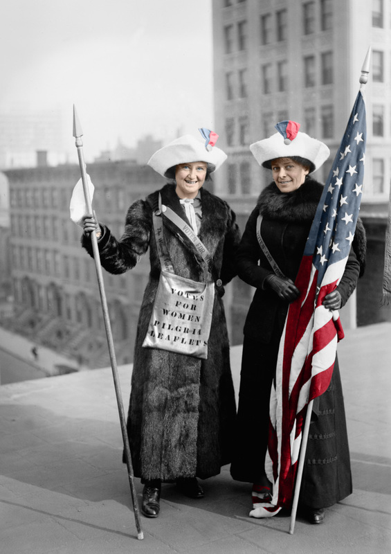 Black and white vintage photo of two women suffragettes with a bag that says Vote for Women. Holding an American Flag that is colorized.